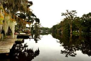 A river lined with docks, houses, and trees in the bayou